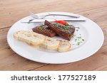 fresh hot grilled beef meat steak served with red hot pepper and white bun slices on plate over wooden table - stock photo