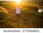 Woman In A Yoga Pose At Sunset...