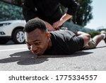 Small photo of selective focus of detained african american man lying on street near policeman, racism concept