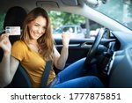 Small photo of Car interior view of woman with driving license. Driving school. Young beautiful woman successfully passed driving school test. Female smiling and holding driver's license.