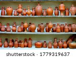 Small photo of Ceramic clay terracotta jug, pot, vase, kitchen souvenirs on shelf at street handicraft pottery shop. Old earthen terracotta jug, pot, clay jar pattern in store. Clay brown various ceramic pot & jugs
