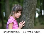 Young Woman Leaning To Tree...