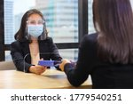 Small photo of Manager from HR department wearing facial mask is interviewing new applicant who is handing her resume and profile through the partition for social distancing, transaction and new normal policy