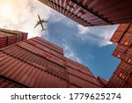 Small photo of Airplane flying above container logistic. Cargo and shipping business. Container ship for import and export logistic. Logistic industry from port to port. Container at harbor for truck transport.