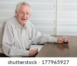 Old Man Holding Glass With...