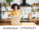 Small photo of A young multi-racial girl received an online delivery order. Attractive woman with Afro hairstyle unpack the box in the kitchen