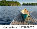 Green Canoe Rest On A Lake...