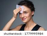 Woman Using Facial Oil Blottin...