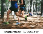 Small photo of Couple running fast through the forest on trail run with motion blur