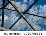 Small photo of Rusty Metal Construction with Barbed Wire against a Blue Sky with light light clouds. Background image symbolizing the restriction of freedom and the opposition of brute strength and fragile nature