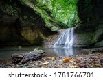 A Low Waterfall In A Cave With...