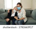 Small photo of Depressed senior mother and daughter wearing medical mask crying and embracing each other grieving loss of loved ones fighting the Coronavirus. People and families affected by COVID-19 outbreak.