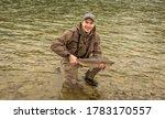 A Fisherman Holding Up A Doe...