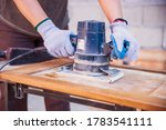 Woman carpenter working with electric machine on wood board in her workshop. Female hands Restoration and repairing old wood home furniture. Woman in carpentry small business  - stock photo