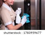 A young girl in uniform wipes the mirror surface of the Elevator. Cleaning service at the hotel. Unrecognizable photo. Cleaning in the hotel Elevator. Copy space.