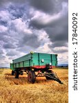 Rural trailer on a harvested field - stock photo