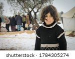 Small photo of Aleppo, Syria, February 15, 2017 A refugee girl looking at the camera, showing signs of cold, due to snowfall