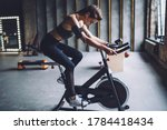 Small photo of Concentrated fit female in sportswear with dark braided hair burning calories on spin bike and listening to music in headphones