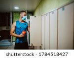 Small photo of A young muscular caucasian man with a medical face mask takes clothes from the closet in the gym locker room. COVID 19 coronavirus protection