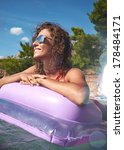 Small photo of Young smiling woman having fun on pink air bed in sea water.
