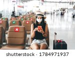 Small photo of Airport terminal social distancing chair form corona virus pandemic. Young adult tourist woman sitting wear mask protect from covid 19. People travel with new normal lifestyle concept.