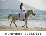 A Chinese Young Woman Riding...