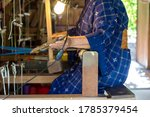 An Elderly Woman Working With...