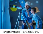 Small photo of Grandfather teaching grandson using telescope to see the constellations and moon. Child seeing satellite using telescope with senior man. Granddad and grandchild using telescope to see moon surface.