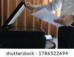 Small photo of Selective focus businessman holding a financial report while using printer in office. Closeup laser printer or scanner. Businessman press button on panel of printer in office. Working in office.