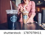 Small photo of Chiang Mai, Thailand : 22/07/2020 : Customer enjoying her coffee break with a cup of Choco-choco Nutty Frappuccino and Cold Brew coffee in Starbucks coffee shop.