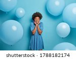 Small photo of Smiling glad dark skinned woman enjoys birthday party, stands with eyes closed and charming smile, wears fancy blue polka dot summer dress, waits for guests poses around inflated balloons, makes photo
