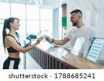 Small photo of Cheerful caucasian male receptionists talking with slim client giving e-key for access to locker room and gym, smiling girl entering training center taking card from happy hospitable man worker