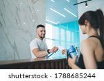 Small photo of Handsome caucasian man receptionist in gym greeting female client giving key to access for training, happy male employee communicating with 20s woman taking card for opening locker room