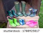 Small photo of Old dirty rubber boots of a big family stand on the wooden floor of a country house porch lit by summer sun with green grass. Short rubber country goloshes.