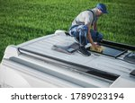 Caucasian Men in His 40s Cleaning Camper Van RV Roof Installed Solar Panels Using Sponge and Soft Washing Detergent. Motorhome Maintenance. RV Industry Theme. - stock photo