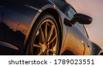 Scenic Sunset Reflection in Supercar Body. Sporty Looking Vehicle with Large Golden Alloy Wheels. Automotive Concept. - stock photo