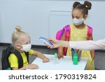 a teacher in the classroom measures the temperature of students. Childrens in medical masks waiting for measure their body temperature with a non-contact thermometer