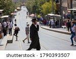 Small photo of Jerusalem / Israel - August 2, 2020: Coronavirus Outbreak. Orthodox Jew with smart phone wearing protective mask crosses a Jaffa Street.