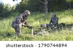 Man in camouflage clothes is chopping wood with axe and throwing it into bonfire. Tourist concept. Hunter checks or cleans hunting rifle. Best friends spend leisure weekend in forest nature background - stock photo