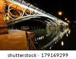Isabel II bridge over Guadalquivir river at sunset with river reflections in Sevilla, Andalusia, Spain - stock photo