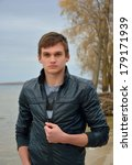 A young man in front of the sea. A young man in a leather jacket in front of the sea and sky