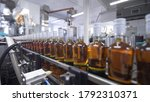 Small photo of Glass bottles filled with alcoholic beverages move along conveyor line with control panel in modern distillery for bottling alcoholic beverages. Factory for bottling prune tincture.