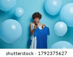 Small photo of Birthday, holidays, clothing concept. Joyful impressed woman stares at smartphone display with surprised happy gaze, gets unexpected message, picks dress on hangers, dresses in everything blue