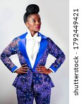 Small photo of Young African woman wearing a stylish pant suit standing with her hands on her hips against a gray background