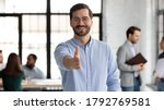 Small photo of Head shot portrait smiling businessman wearing glasses extending hand for handshake at camera, friendly hr manager greeting candidate on interview, offering deal, welcoming client at meeting
