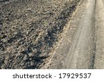 rural road near the fallow field - stock photo