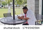A black young doctor using doctor uniform looking at his smartphone while sitting on a cafe table. - stock photo