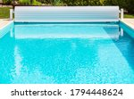 Brand New White Solar Pool Cover Roller Shutter With Crank. Open Swimming Pool. - stock photo
