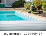 New Grass Turfs Installation Next to Residential Swimming Pool in the Backyard Garden. Caucasian Professional Landscaper at Work. - stock photo