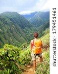 Hiking woman on Hawaii, Waihee ridge trail, Maui, USA. Young female hiker walking in beautiful lush Hawaiian forest nature landscape in mountains. Asian woman hiker wearing backpack looking at view.